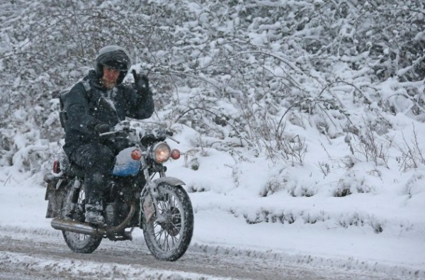 A Motorcycle rider riding his bike in heavy snowfall