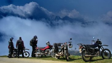 A group travel bikers is standing bsides the road to capture view from the top