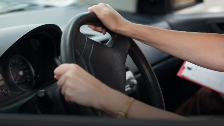 A car driver holding handle of car during licence exam