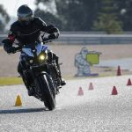 A bike rider testing motorbike on a racing track