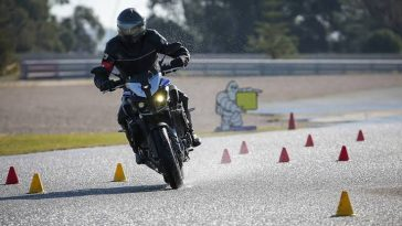 A bike rider testing motorbike on a racing track