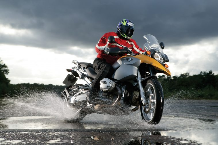 A rider driving bike on wet road after rain