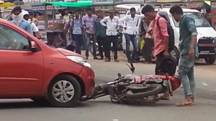 A motorcycle is being hit by a car hit the motorbike bike on the road